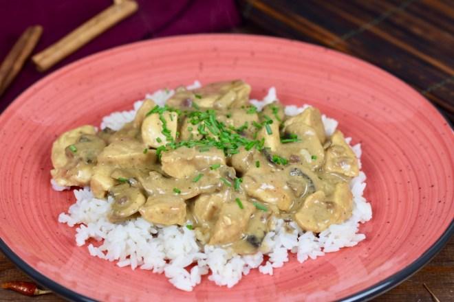 Hähnchen-Geschnetzeltes mit Pilzen auf Reis auf einem roten Teller, dekoriert mit Schnittlauchröllchen. Hintergrund dunkel