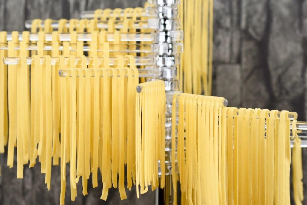 frische Tagliatelle zum trocknen aufgehängt auf Nudelständer, Hintergrund schwarz