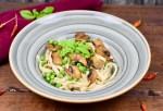 Tagliatelle mit Pilzen und Erbsen in einem tiefen grauen Teller, garniert mit Basilikum. Dunkler Hintergrund