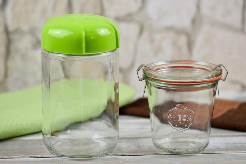 Ein Glas zum Einwecken mit Deckel und ein anderes Glas mit hellgrünem Plasikdeckel stehen vor hellem Hintergrund.