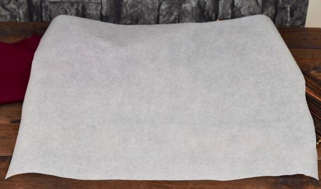 Ein Blatt weißes Backpapier auf dunklem Untergrund.