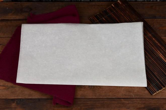 Ein Blatt weißes Backpapier einmal in der Mitte gefaltet. Hintergrund dunkel.