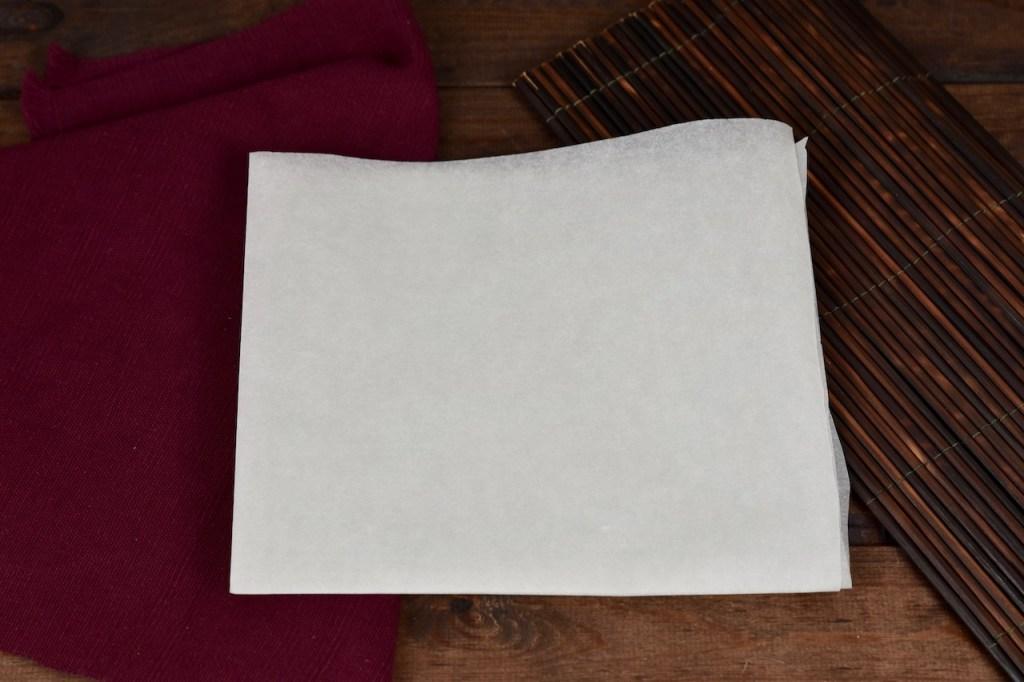 Ein Blatt weißes Backpapier 2 mal gefaltet. Hintergrund dunkel.