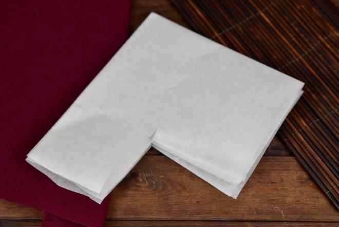 Ein Blatt weißes Backpapier 2 mal gefaltet. An einer Ecke ist ein Stück rausgeschnitten. Hintergrund dunkel.