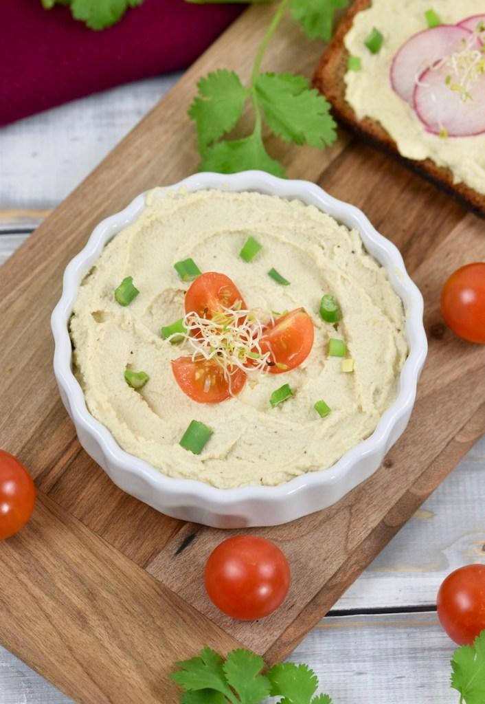 Veganer Frischkäse in weißer Schale, die auf einem Holzbrettchen steht. Der Frischkäse ist mit Vierteln von Cocktailtomaten, Frühlingszwiebel und Sprossen garniert. Im Hintergrund liegt eine Scheibe Brot mit Frischkäse und Radieschen.
