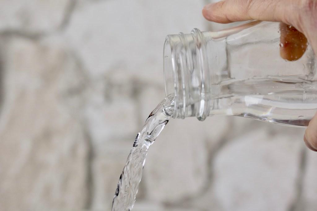 Wasser wird aus einer Glasflsche geschüttet. Hintergrund hell.