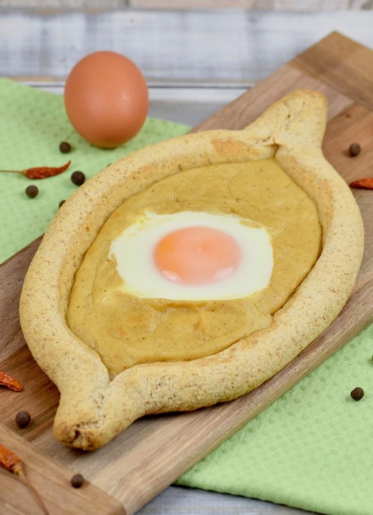 Chatschapuri mit Ei und Senfsauce auf länglichem Holzbrettchen. Heller Hintergrund dekoriert mit einem Ei, getrockneten Chilischoten und Pimentkörnern.