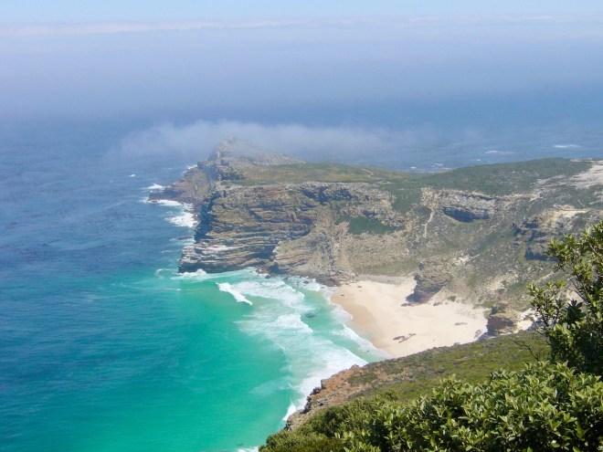 kleiner weißer Strand mit türkisem Meer und schroffen Felsen von oben fotographiert. Kap der guten Hoffnung - Südafrika