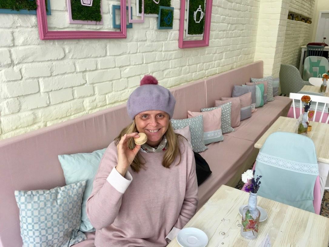 Über mich - Ich in einem Cafe mit Macaron in der Hand