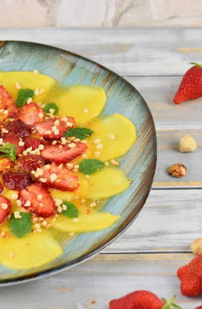 Erdbeer-Mango-Carpaccio mit Minze und Orangen-Dressing auf türkisem Teller garniert mit Minze und Haselnusskernen. Hintergrund weiß. Teller nur halb zu sehen.