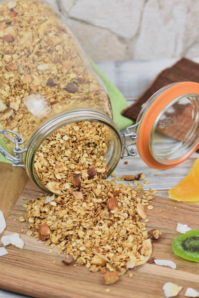 Knuspriges Granola, das aus einem liegenden Glas geschüttet wurde. Das ausgeschüttete Granola liegt auf einem Holzbrett und der Hintergrund ist hell.