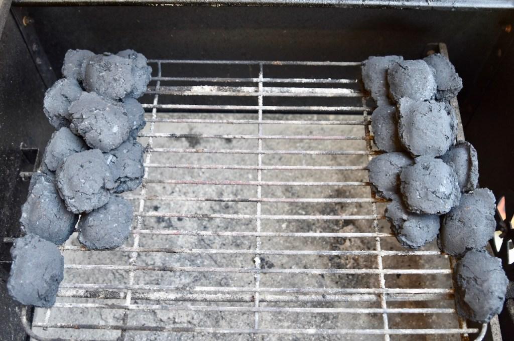 Holzkohlebriketts im Grill in Reihen aufgeschichtet (Minionreihen)