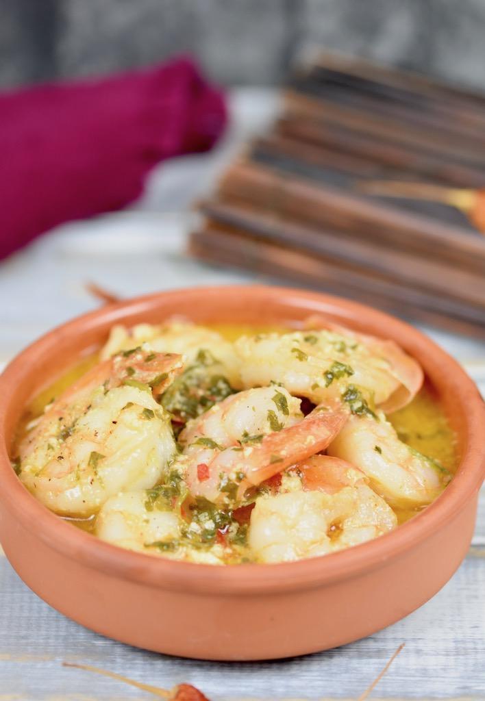 Gambas al Pil Pil in einer Knoblauch-Weißwein-Sauce in einer Tonschale. Hintergrund hell.