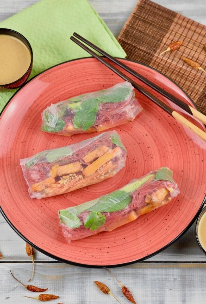 Drei Sommerrollen mit grünem Spargel und Süßkartoffel auf einem roten Teller. Auf dem Teller liegen auch Stäbchen. Im Hintergrund sieht man zwei Schälchen mit Erdnusssauce.