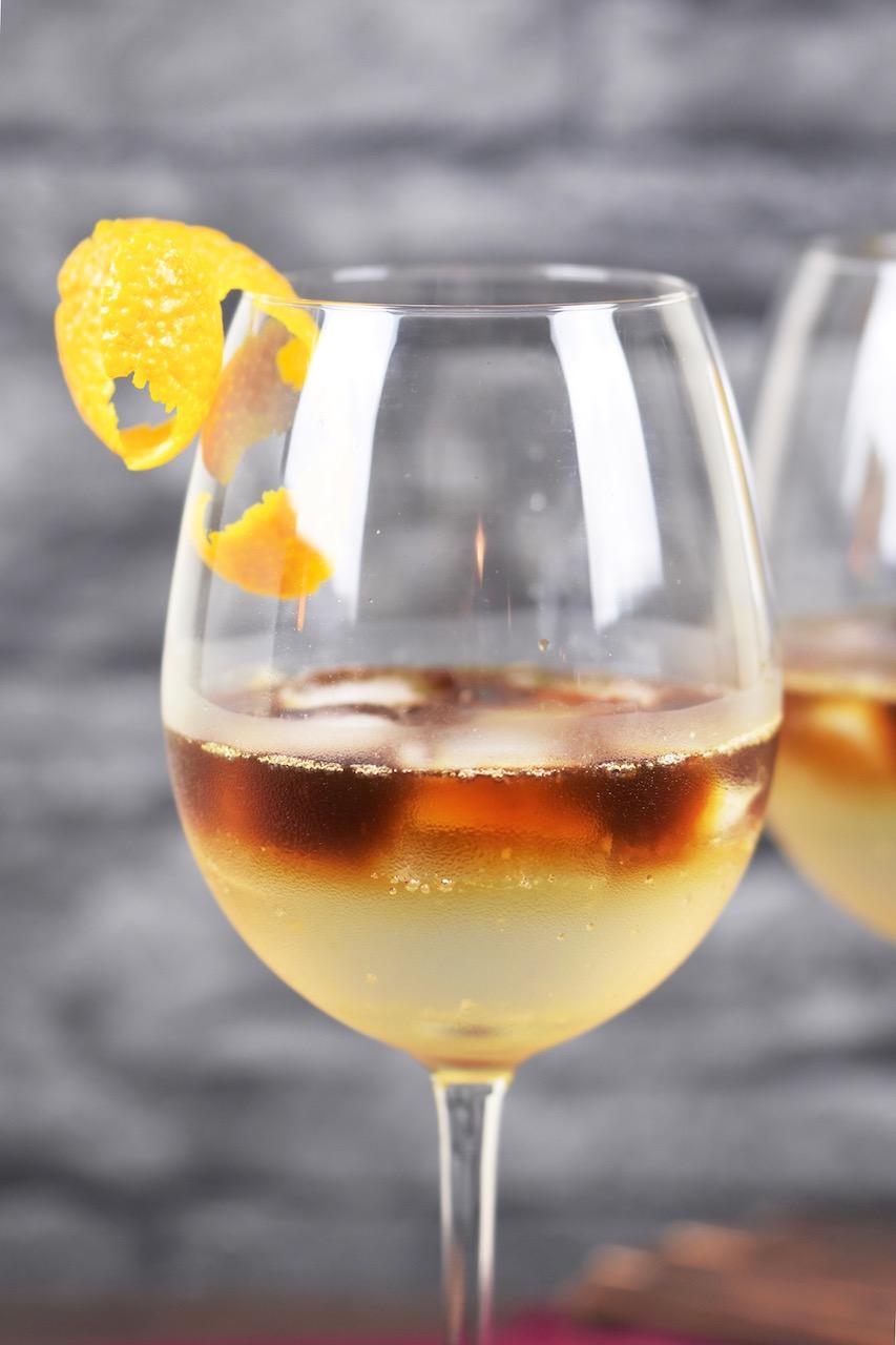 Espresso Tonic im Weinglas. Hintergrund dunkel.