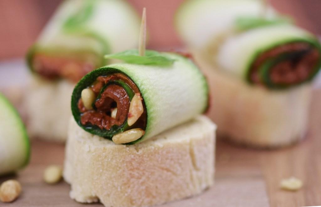 Zucchini-Röllchen mit Paprikacreme und Pinienkernen gefüllt auf Holzbrett.