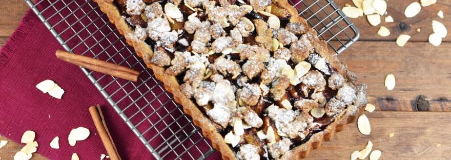 Glutenfreie Pflaumen-Tarte mit Zimtstreuseln. Hintergrund dunkel.