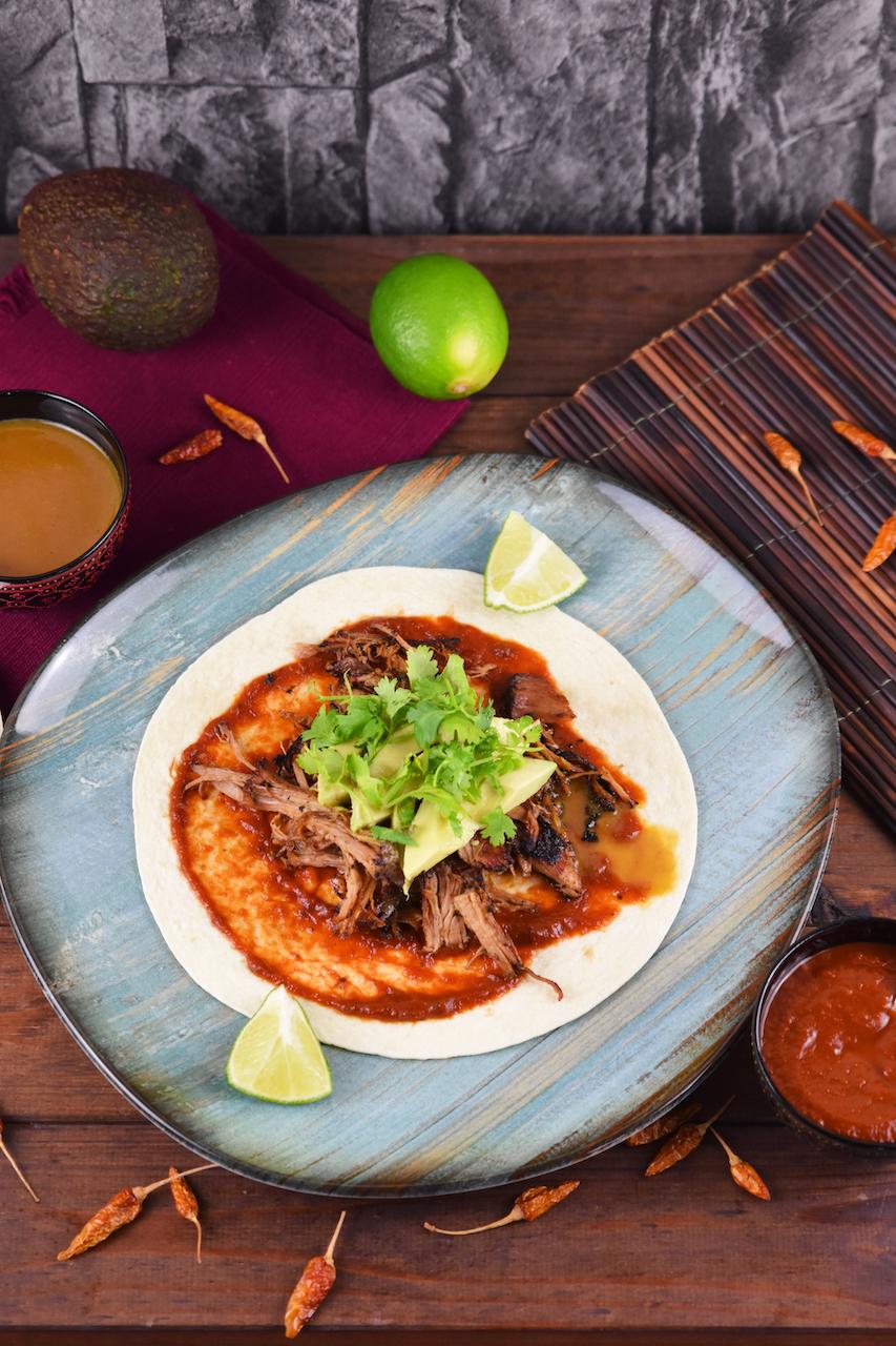 Mexikanische Carnitas mit Salsa de Chipotle, Avocado und Koriander auf Tortilla. Hintergrund dunkel.