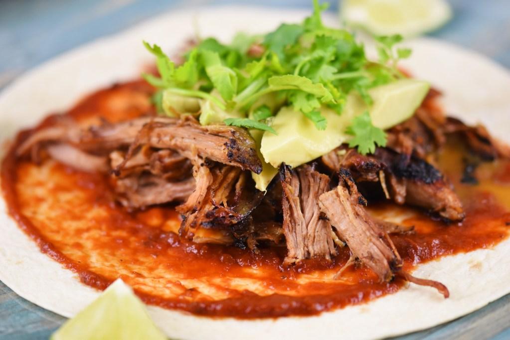 Mexikanische Carnitas mit Salsa de Chipotle, Avocado und Koriander auf Tortilla. Hintergrund blau.