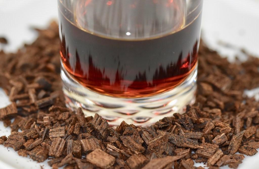 Vanillearoma in kleinem Glas. Das Glas steht zwischen zerkleinerten Vanilleschoten.