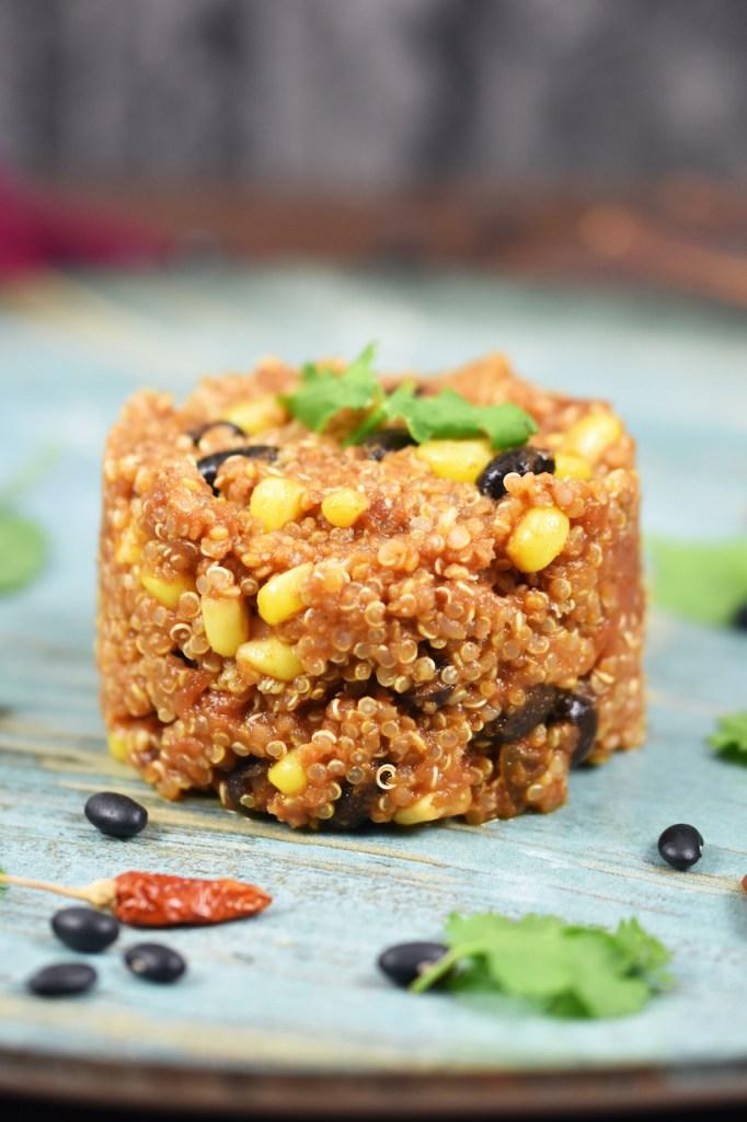 Quinoa-Pfanne auf mexikanische Art auf blauem Teller. Hintergrund dunkel.