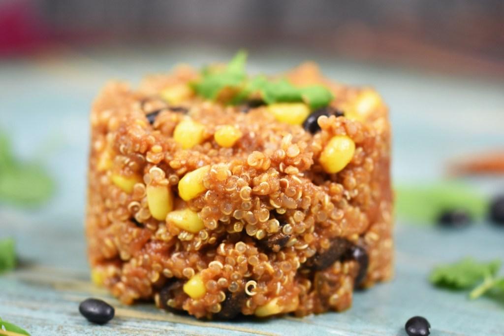 Quinoa-Pfanne auf mexikanische Art auf blauem Teller.