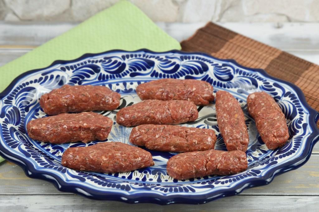 Mehrere rohe Mici oder Mititei auf einem ovalen Teller mit blauem Muster. Hintergrund hell.