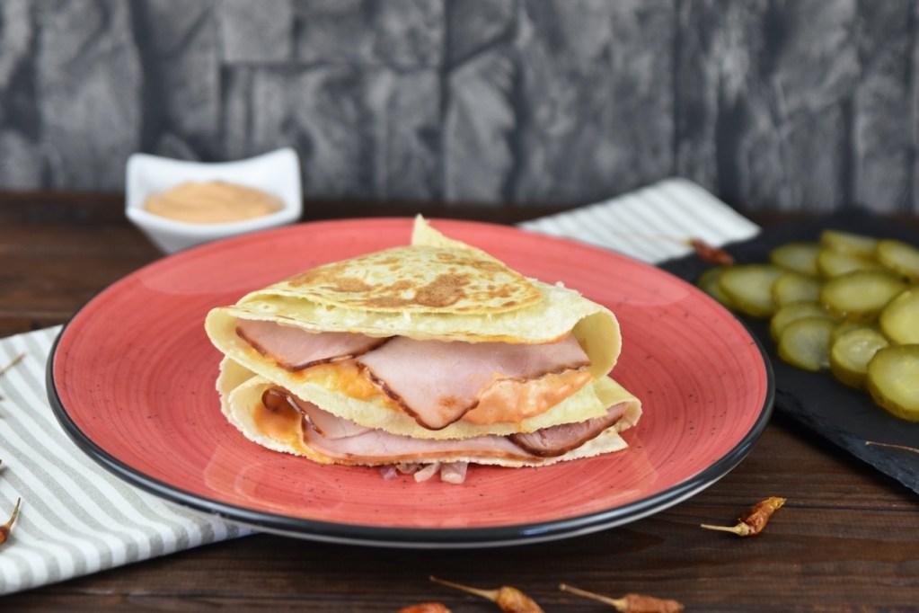 Reuben Sandwich-Tortilla Wrap auf rotem Teller. Hintergrund dunkel.