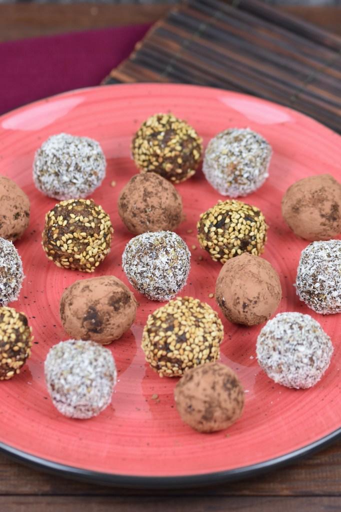 Glücksbällchen - Bliss Balls - ummantelt mit Kakaopuler, Kokosraspeln oder Sesam auf rotem Teller.