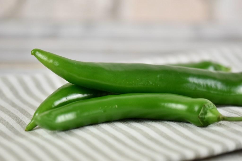 Drei grüne Chilis auf heller gestreifter Stoffserviette.