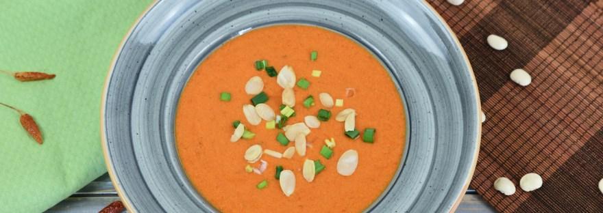 Cremige Paprikasuppe mit Kräutern in einem grauen Teller.