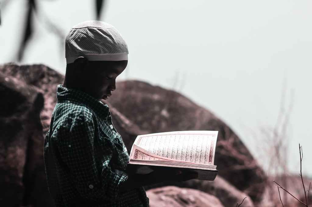 photo of boy holding religious book