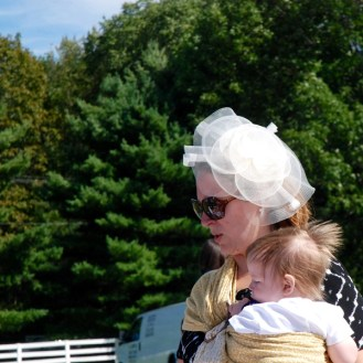 polo match spectator wearing fascinator holding baby