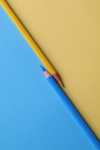 Blue and yellow colored pencils with blue and yellow paper