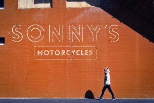 Zirkus Design | Logo Design for Veteran - Owned Businesses - Sonny's Motorcycles : Retro Stamped Text Concept Street Wall Mockup