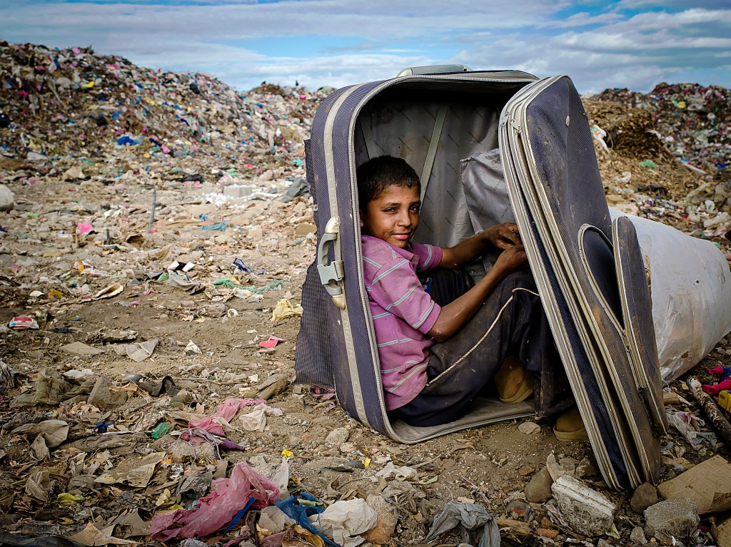 A boy takes a break from sorting recyclables inside a suitcase to protect himself from the high winds blowing filth around. Masaya, Nicaragua. Photo by: Timothy Bouldry, 2015.