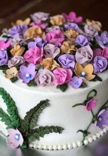 A springtime flower cake decorated with gum paste flowers and rose | Photo by Zoë François