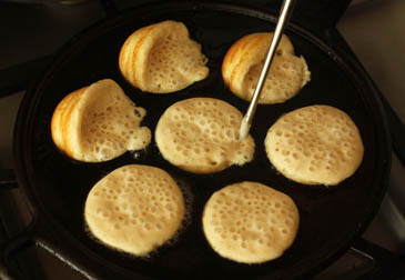 Flipping partially baked aebleskivers in a pan |Recipe | ZoëBakes | Photo by Zoë François