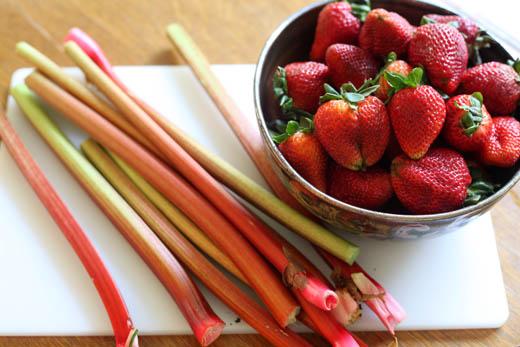 Bowl of strawberry and bunch of rhubarb | ZoëBakes | Photo by Zoë François