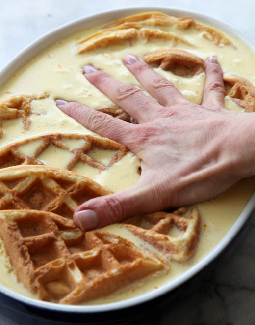 Pressing waffles down to soak in the bread pudding custard | photo by Zoë François