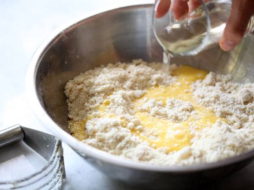 The best apple pie recipe - adding the whisked egg, water and vinegar to the flour/lard mixture | photo by Zoë Francois