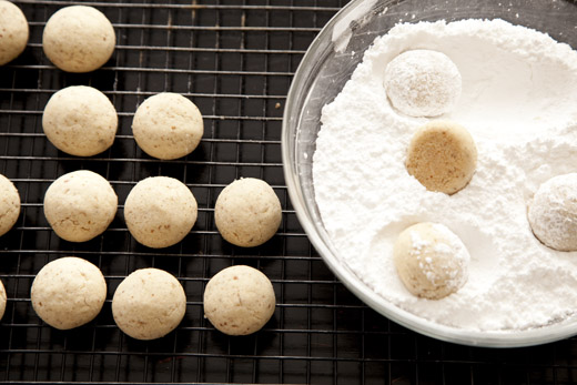 Dipping Russian tea cakes in powdered sugar