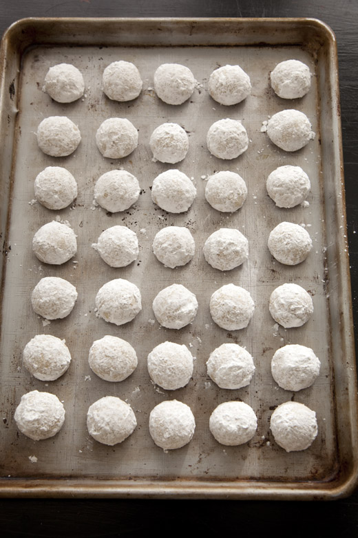 Russian tea cakes (Mexican wedding cookies) on a sheet pan after dipping in confectioners' sugar