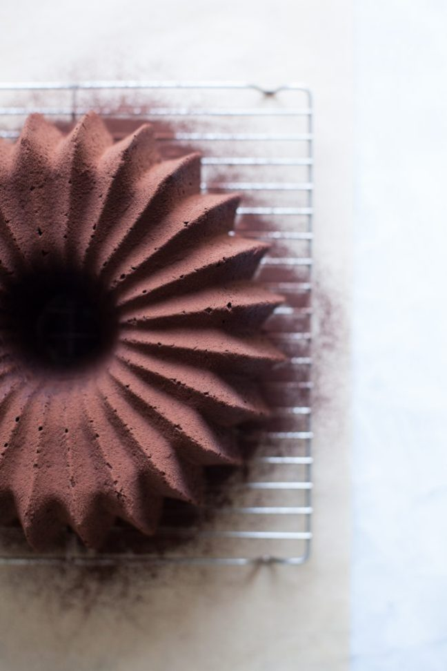 Chocolate Bundt Cake dusted with cocoa powder on a cooling rack | Photo by Zoë François