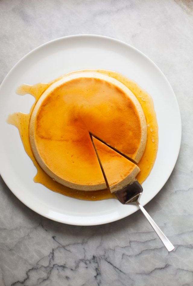 Flan on a plate with one slice cut out, sitting on a server.