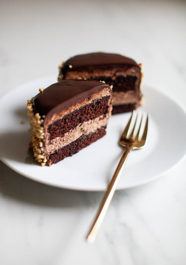 A cross section of a Chocolate Peanut Butter mini cake on a white plate with a gold fork.