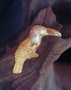 In this example of fine art jewelry, the pearl bird brooch, a Toucan has been rendered in 22 karat gold around a suggestively shaped baroque pearl