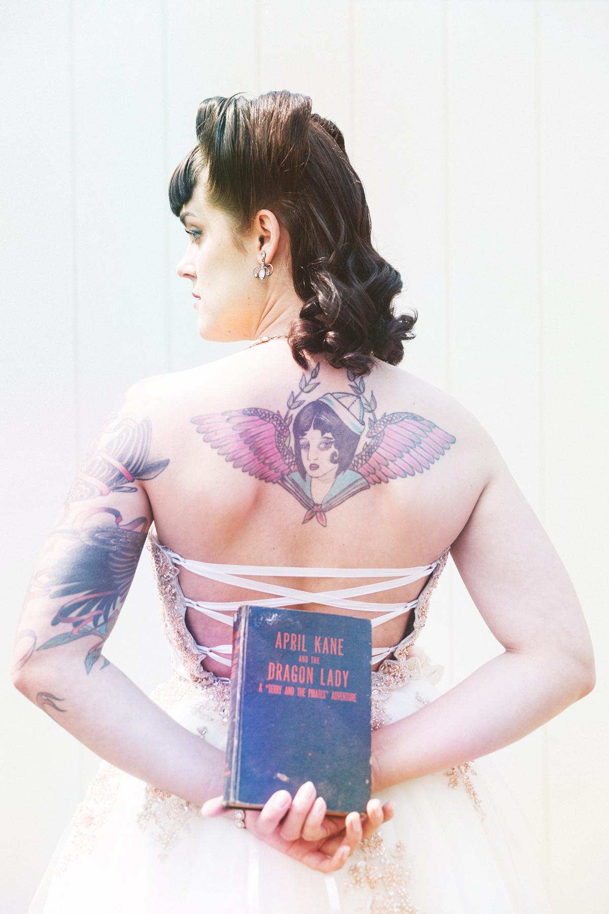 tattooed bride holding book behind her