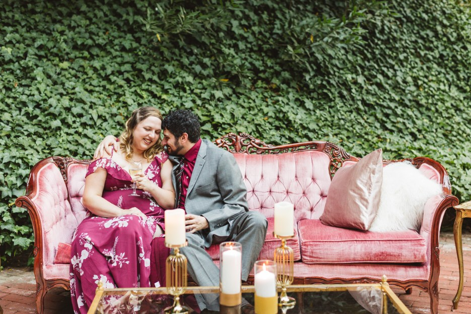 wedding guests canoodling on a pink couch