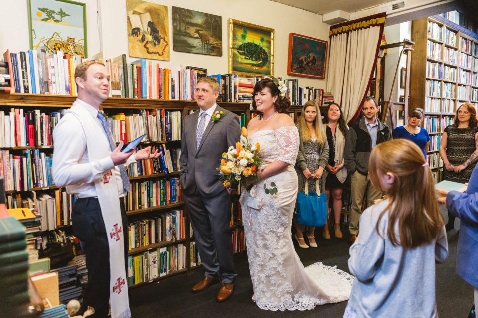 people getting married in a small bookstore at an intimate, quirky offbeat wedding | Small wedding ideas - should I even have a small wedding?